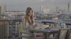 Young woman eating on a rooftop, ungraded, slog2 Stock Footage