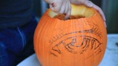 Scraping out Halloween pumpkin - stock footage