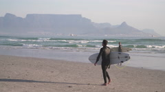 Surfers walking on Beach with Table Mountain in Distance, Cape Town - stock footage