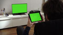 Man Holds Tablet And Watches Television Green Screen - stock footage