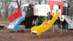 Kids play slide on a outdoors playground in a park Stock Footage