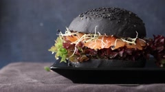Two homemade black burgers with salted salmon, beetroot cutlet, sprouts and Stock Footage