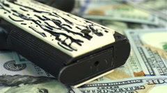 Dollar bills and black gun Stock Footage