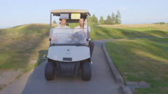 Golfers look around from golf cart Stock Footage