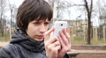 Female type slide her smartphone touchscreen outdoors in park Footage