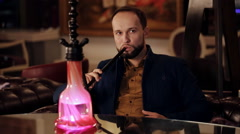 Man smoking a traditional Middle Eastern Hookah. Stock Footage