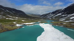 Flying down to the frozen lake in mountain pass in Norway Stock Footage
