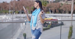 Grinning woman using phone on overpass Stock Footage