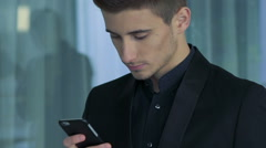 A sincere young man looking at the phone. distracted and smiling. Slow motion. Stock Footage