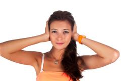 Stock Photo of Hear no evil. Young pretty woman covering her ears