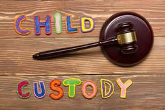 Judge gavel and colourful letters regarding child custody, family law concept - stock photo