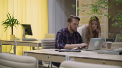 The guy with the girl talk looking at the computer Stock Footage