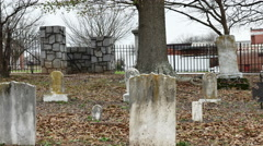 Tilt up-Gravestones to barren tree in cemetery Anderson South Caro Stock Footage