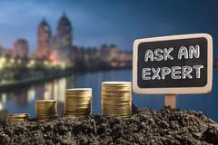 Ask an expert. Financial opportunity concept. Golden coins in soil Chalkboard on - stock photo