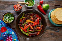 Beef fajitas in a pan with sauces Mexican food - stock photo