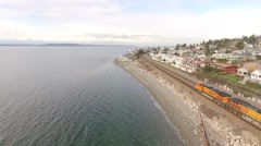 Aerial - Chasing Freight Train on shoreline of Puget Sound Seattle Washington 2 Stock Footage