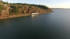 Chasing Sound Transit Train on shoreline of Puget Sound Seattle Washington Stock Footage