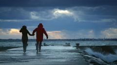 young couple running in front of the storm waves - stock footage
