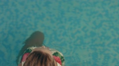 Beautiful girl in the bright bathing suit looks at the camera lie down on the Stock Footage