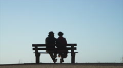 Barefoot couple sitting on windy park bench, Cape Town, South Africa Stock Footage