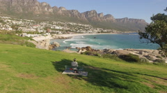 Aerial of Man on Bench, Camps Bay Coastline, Cape Town Stock Footage