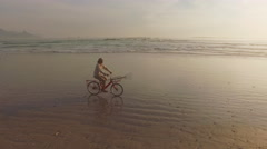 Aerial of Man Riding Bike on Beach, Table Mountain Stock Footage
