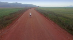 Aerial of Man Riding Bicycle on Dirt Road Between Lush Green Field, Landscape Stock Footage