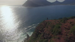 Aerial of Man Looking Out at Ocean, Chapmans Peak, Cape Town Stock Footage