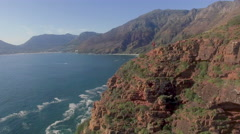 Aerial of Man on Cliff Looking out at Ocean, Chapmans Peak, Cape Town Stock Footage
