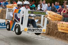 Competitors Racing Bus Vehicle Get Airborne At Soap Box Derby - stock photo