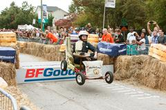 Man Steers Furniture Vehicle Over Ramp In Soap Box Derby - stock photo