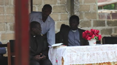 PRIESTS SITTING AT A TABLE - SPEAKER AT A CEREMONY Stock Footage