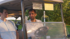 Golfers talk on golf cart Arkistovideo