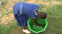 FEMALE STUDENTS RINSES OUT GREEN BUCKET Stock Footage