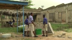 MALE STUDENTS FILL WATER BUCKET AND CARRY IT TO HAND-WASHING STATION Stock Footage