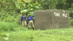 STUDENTS CUTTING GRASS WITH MACHETES BY OUTDOOR TOILETS MARKED MALE AND FEMALE Stock Footage
