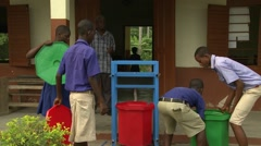 STUDENTS LIFT GREEN BUCKET ONTO HAND-WASHING STATION Stock Footage