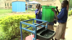 STUDENTS LIFT A GREEN BUCKET ONTO A HAND-WASHING STATION Stock Footage