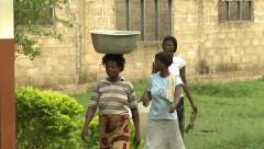 THREE WOMEN WALK BY SCHOOL, ONE WITH TUB OF WATER ON HEAD Stock Footage