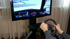 Young boy plays a virtual racing video game - stock footage