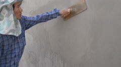 Worker using trowel to finish wet concrete wall at construction site Stock Footage