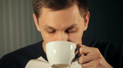 Young man drinks tea from a white cup Stock Footage