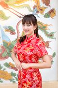 Stock Photo of Happy Chinese new year. Cute Asian woman with gesture of congratulation