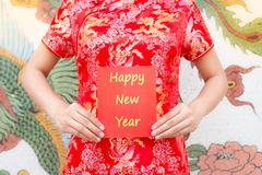 Happy Chinese new year Asian woman with red Cheongsam holding a red packet Stock Photos
