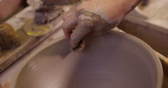 Close-up shot of a man making a ceramic pot in a workshop. Slow motion. Stock Footage