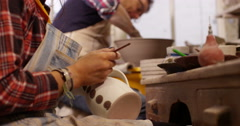 Close-up shot of a young woman at workbench painting ceramics in pottery studio. - stock footage
