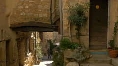 People standing next to a passageway with arch in Tourrettes-sur-Loup - stock footage
