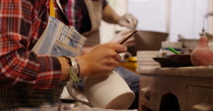 Young woman at workbench painting ceramics in pottery studio. Slow motion. - stock footage