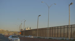 Vehicles on Highway by Border Fence Stock Footage
