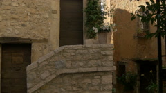 Narrow street with stone buildings and flowers in Tourrettes-sur-Loup Stock Footage